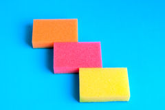 Colored sponges. Three kitchen sponges colored on blue background Royalty Free Stock Photo
