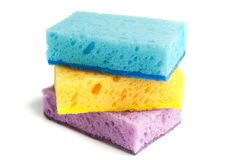Colored sponges for washing dishes and other domestic needs. Yellow sponge lies between the blue and purple sponges at a slight stock image