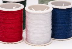 Colored spools of string on white background. Clos-up of colored spools of string on white background Royalty Free Stock Images