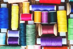 Colored spools of thread laid out in rows on wooden background.  royalty free stock photos