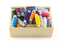 Colored spools with thread in wooden box isolated close up Royalty Free Stock Images
