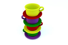Colored stacked coffee frosted cups on white. Colored stacked coffee frosted cups and saucer on white backgrou Stock Image