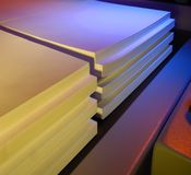 Colored stacked paper. Stacked paper just cut into neat rows lit with colored lights stock photo