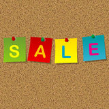 Colored stick notes with word SALE pinned to a cork message boar Royalty Free Stock Image
