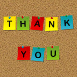 Colored stick notes with words thank you pinned to a cork messag. Colored stick notes with words thank you pinned with push pins to a cork message board Royalty Free Stock Photography