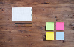 Colored stickers, notebook and pencil on  table. Royalty Free Stock Photography