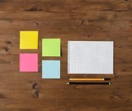 Colored stickers, notebook and pencil on wooden Royalty Free Stock Photo