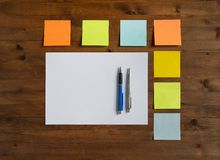 Colored stickers, sheet of paper and two pens Stock Images
