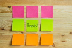 Colored stickers on a wooden background. A set of stickers or sheets of paper on a wooden background. A thank you note on the sticker in the center. Horizontal Royalty Free Stock Image