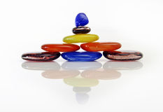 Colored Stones. Colorful stones stacked in layers and reflected on white surface Stock Photo