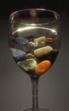 Colored stones in a glass of water Stock Images