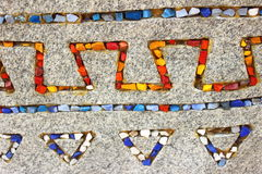 Colored stones. On a gray granite stone with colored stones laid ethnic pattern Stock Image