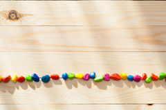 Colored stones on textured board in sunny weather with light from the window.. Royalty Free Stock Image