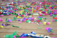 Colored streamers confetti scattered on the wooden plank floor. Happy party background. Stock Photos
