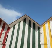 Coloured striped beach huts in the summers sun. Colored striped beach huts in the summers sun, red, green and yellow Royalty Free Stock Photos