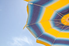 Colored striped sun umbrella, blue sky, outdoor, half close up Royalty Free Stock Photos