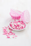 Colored sugar hearts and paper baking dishes, vertical, close-up Stock Image