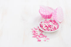 Colored sugar hearts and paper baking dishes on white wood Stock Image