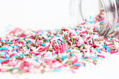 Colored sugar sprinkles and its container Royalty Free Stock Photos