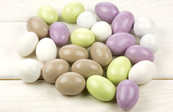 Colored sugared almonds. On white wooden background royalty free stock photos