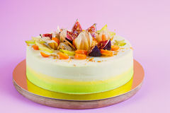 Colored summer cake with fruit on pink background Royalty Free Stock Photos