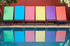 Colored sun loungers by pool. Colorful sun loungers in a row next to a swimming pool royalty free stock image