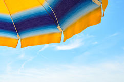 Colored sun umbrella, blue sky, outdoor, half close up Stock Image