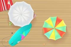 Colored sun umbrellas, surfboard, flip-flops and a beach Mat on the wooden backgroun Stock Photos