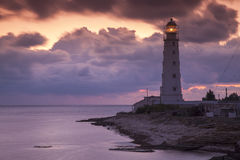 Colored sunset and lighting lighthouse on the sea coast Stock Photos