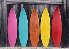 Colored surfboards leaning up against a wooden fence Stock Image