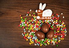 Colored sweets, gingerbread figure hare, chocolate eggs. Stock Photography