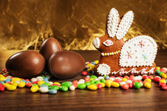 Colored sweets, gingerbread figure hare, chocolate eggs. Stock Photo