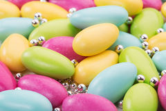 Colored sweets. Heap of sugared almonds and silver dragees stock images