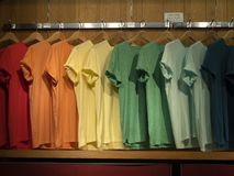 T-shirts of red, orange, yellow, Green and blue colors, short sleeves in the shop WINDOW. stock photography