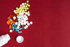Colored tablets in plastic container top view Stock Photos