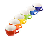 Colored tea cups and saucers. Colored tea cups and saucers, isolated on white Stock Image