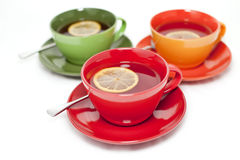 Colored tea cups with tea and lemon Stock Images