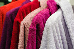 Colored terry bathrobes hanging on the store trempel Stock Images
