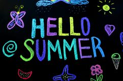 Colored text hello summer on blackboard. stock images