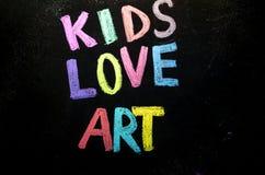 Colored text kids love art on blackboard.  stock photo