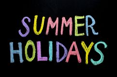 Colored text summer holidays on blackboard.  royalty free stock photos