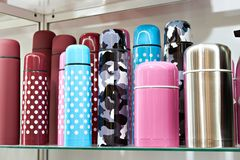 Colored thermos in shop Stock Photos
