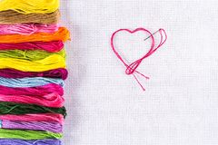Colored thread for embroidery on white canvas, a needle with red thread in the shape of a heart. The concept of love for a hobby. Colored thread for embroidery Royalty Free Stock Images