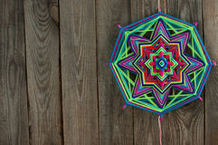 Colored thread mandala with free space for text.