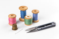Colored thread with scissors on white background. The Colored thread with scissors on white background Stock Photo