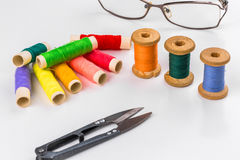 Colored thread with scissors on white background. The Colored thread with scissors on white background Stock Images