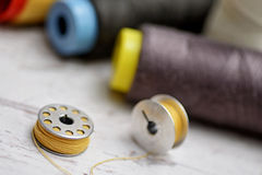 Colored threads. Colorful spools of thread on a wooden table Royalty Free Stock Image