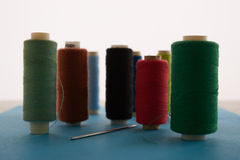 Colored threads and needle Stock Images