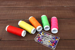 Colored threads on wooden background. Sewing kit. Set for needlework Stock Photo