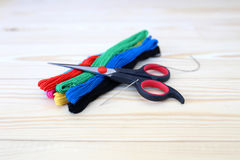Colored threads on wooden background. Sewing kit. Set for needlework Stock Photos
